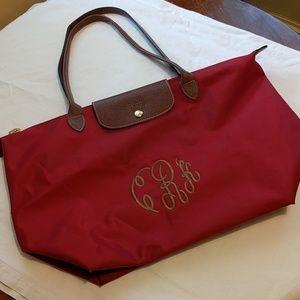 Longchamp le pliage red monogrammed bag